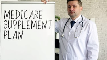A doctor stands next to a dry erase board with Medicare Supplement Plan written on it