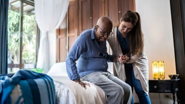 A nurse helps a nursing home resident get out of bed