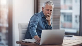 Cropped shot of a thoughtful mature businessman working on a laptop in an office