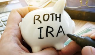 Hands holding piggy bank with Roth IRA. Pension plan.