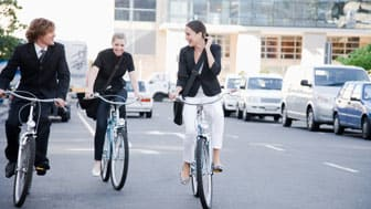 Businesspeople riding bicycles in city street