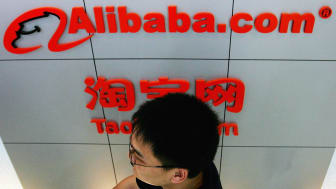 BEIJING - AUGUST 12: A man walks past the logo of Alibaba (China) technology Co., Lth on August 12, 2005 in Beijing, China.Yahoo Inc. signed a deal to buy 40 percent of Alibaba.com for EUS 1