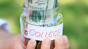 Hand holding a jar of money for college