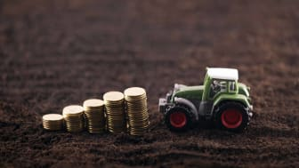 A small tractor pushing around pennies, illustrating smaller stocks