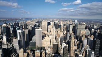 a shot of New York city from above with its skyscrapers and blue sky streaked with clouds