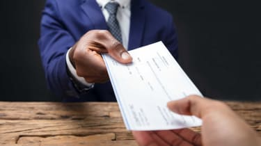 Person handing another person a paycheck