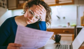 A woman looks through her bill in frustration.