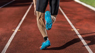 A man runs in his lane on a track.