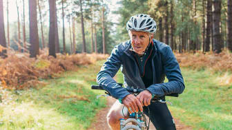 Older man on a bike in the woods.