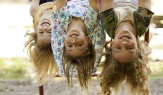Three sisters hang upside down at playground.