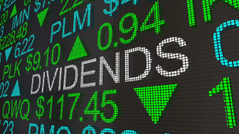"""The word """"dividend"""" appears on an electronic stock ticker board."""