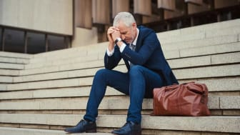 Senior man sits on a building outside staircase with his head in his hands