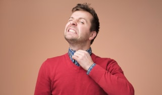 Man tries to loosen his collar, which is too tight.