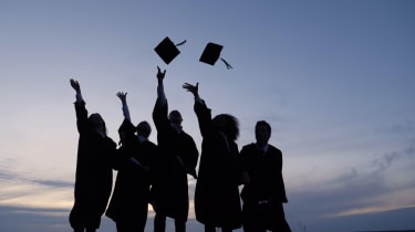 Graduates throw their caps into the air.