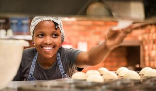 A small-businesswoman smiles at a bakery.