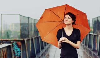 Woman standing under an orange umbrella in the rain