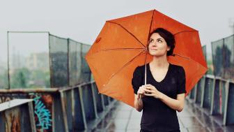 Woman standing under orange umbrella in the rain