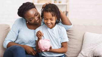 Mom with young daughter putting coin in piggybank
