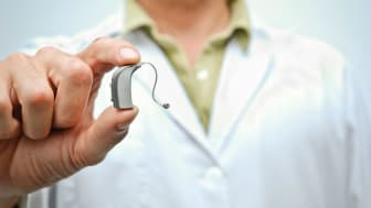 A person holds hearing aids