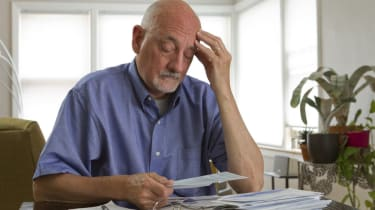 Older man looking frustrated while reviewing bills