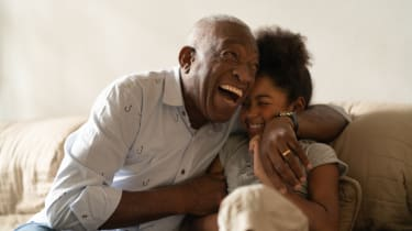 A grandfather hugs his granddaughter while laughing
