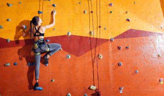 A woman scaling an artificial rock climbing wall