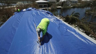Two roofers put a blue plastic tarp over a residential roof