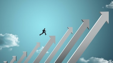 businessman jumping on growing chart with sky background