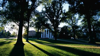 The Lyceum, a Greek Revival-style building at the University of Mississippi, is seen through the trees.