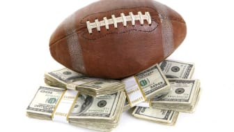 picture of a football sitting on a pile of money