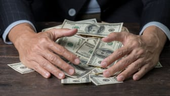 picture of man pulling in a pile of money on a table