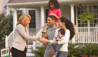 Realtor meeting young couple and their child at a house for sale