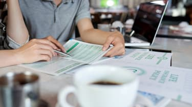 Close-up shot of unrecognizable young family sitting at cafe table and reading life insurance brochure, blurred background