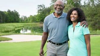 Smiling senior couple walking on golf course