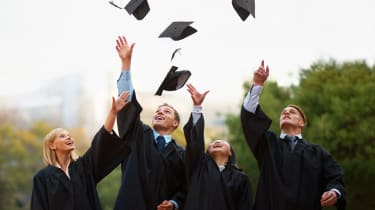A group of students throwing their caps into the air after graduation