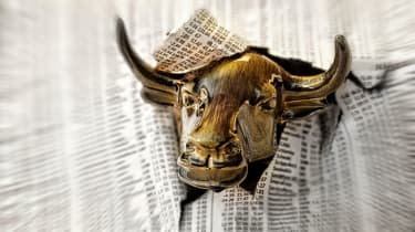 picture of wall street bull charging through a newspaper's financial page