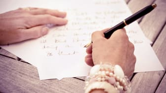 Person writing letters with black pen and white paper.