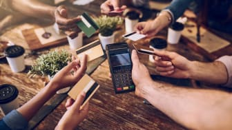 High angle shot of a group of friends offering their bank cards to pay the bill at a cafe