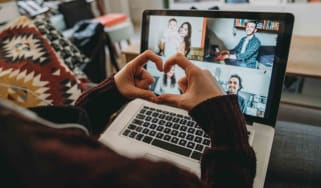 Person making heart with fingers while on a web camera call