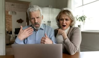 A couple looks at a computer screen with a shocked expression