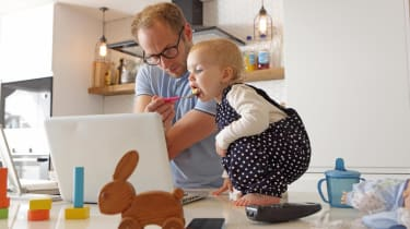A dad working at home feeds a toddler at the same time.