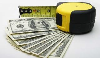 A measuring tape measures a fan of $20 bills.