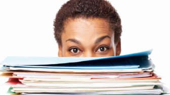 A woman peeks out above a pile of paperwork.