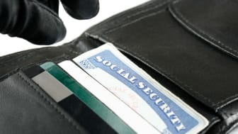 Gloved fingers of a thief stealing a Social Security card from a wallet