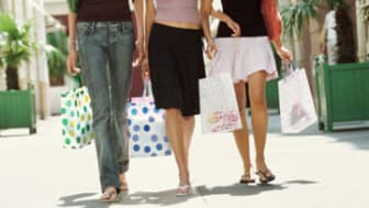 Low Section of Three Teenage Girls Walking Towards the Camera Holding Shopping Bags