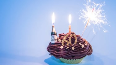 """Sparklers and a """"60"""" candle adorn a chocolate cupcake."""