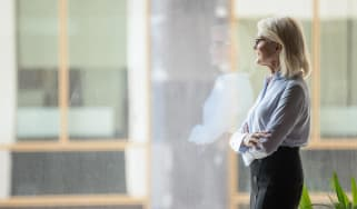 Career woman thinks as she looks out a window