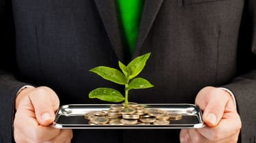Person holding tablet with coin money on it and a leave growing out of the coins