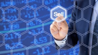 Businessman in a blue suit pressing the sell button an a hexagon grid n front of a stock ticker wall