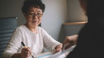 senior woman having discussion with her agent about her retirement investment plan signing legal document